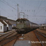 E 44 017 hat die Wagen aus der Hinterstellanlage in Nürnberg-Dutzendteich geholt, fährt am 16. April 1972 in Nbg.-Hbf. Gleis 1 ein und wird wenig später Pendler nach Bamberg bringen.